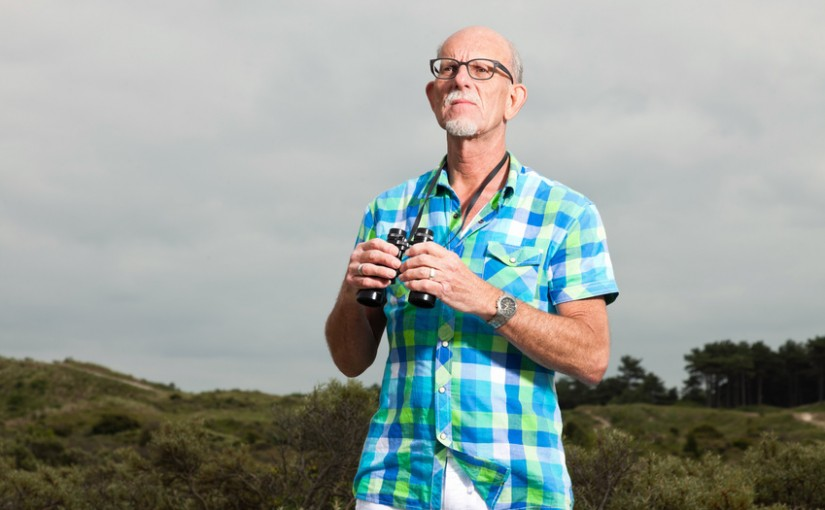 Senior man with beard and glasses using binoculars outdoors in grass dune landscape. Wearing green blocked shirt.